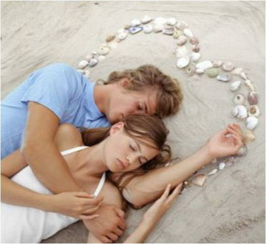 Couple laying on beach with a heart of shells
