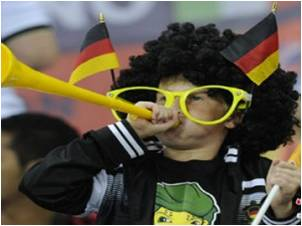 German child football fan in costume and blowing vuvuzela